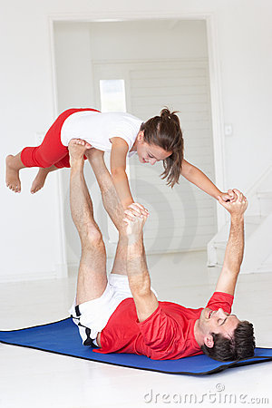 Father and daughter doing yoga lift