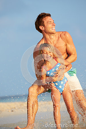 Father And Daughter Having Fun In Sea On Beach Holiday