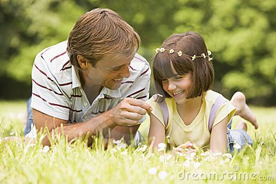 Father and daughter lying outdoors with flowers