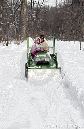 Father and daughter plow a snowy drive on a tractor
