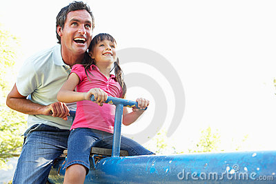 Father And Daughter Riding On See Saw In Playgroun