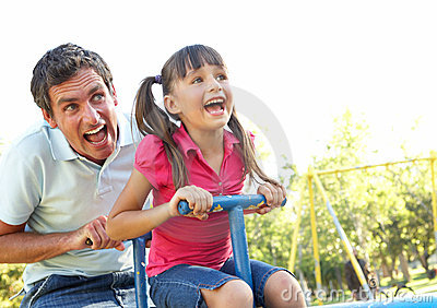 Father And Daughter Riding On See Saw In Playground