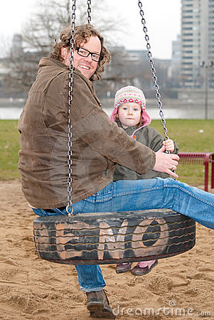 Father and daughter swinging