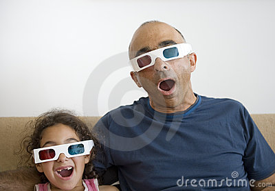 Father and daughter watching television in 3D