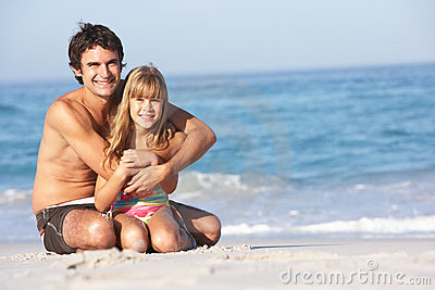 Father And Daughter Wearing Swimwear Sitting Down