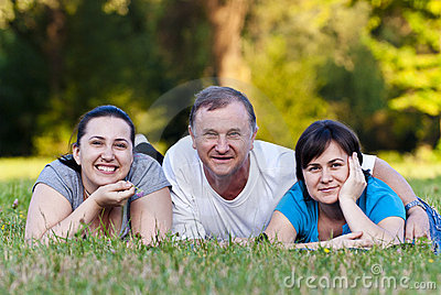 Father and daughters on grass