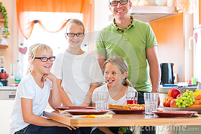 Father and daughters in kitchen eating healthy