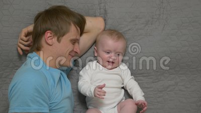 Father Exercise Baby. Stretches young man 30 years old in blue t shirt lying on the bed with newborn boy son in white bodysuit caucasian white european stock footage