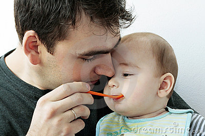 Father feeding his little baby