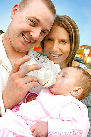 Father feeds milk to baby