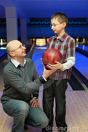 Father gives son ball for bowling