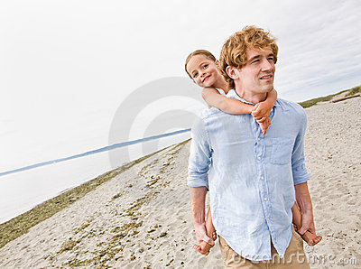 Father giving daughter piggy back ride at beach