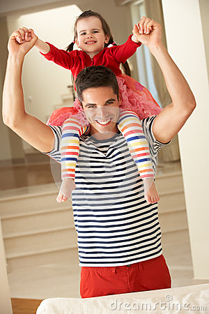 Father Giving Daughter Ride On Shoulders At Home