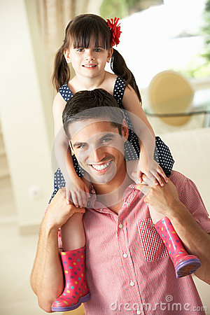 Father Giving Daughter Ride On Shoulders Indoors