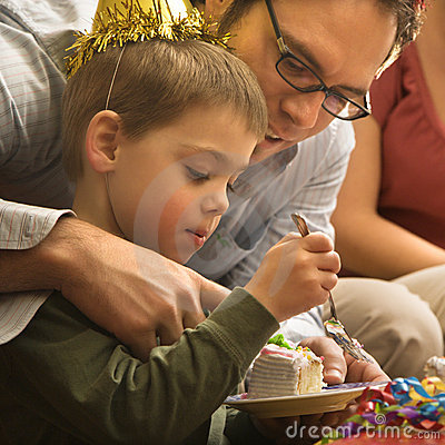 Father helping boy with cake.