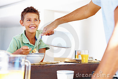 Father helping son at  breakfast