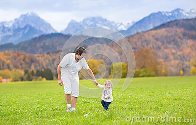 Father with his baby daughter in field in mountains