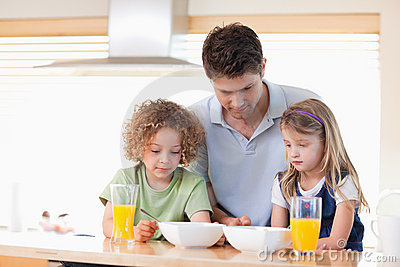 Father with his children having breakfast