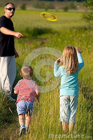 Father and his children play with frisbee