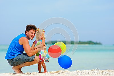 Father and his cute daughter on exotic beach