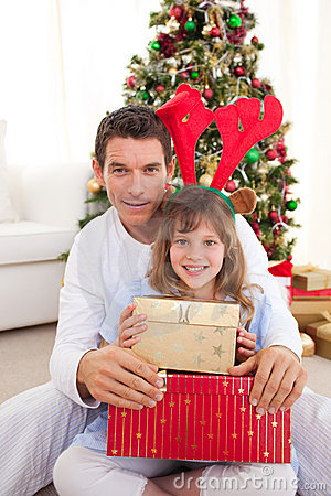 Father and his daughter opening Christmas gifts