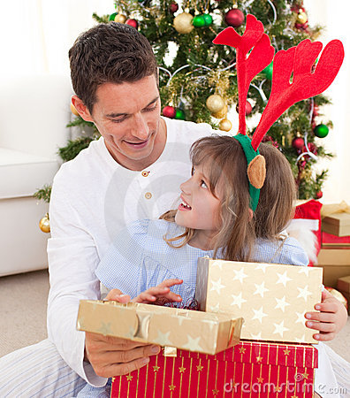 Father and his daughter opening Christmas present