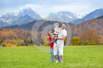 Father with his kids in field in snow mountains
