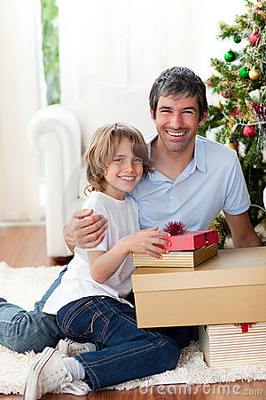 Father and his son opening Christmas gifts