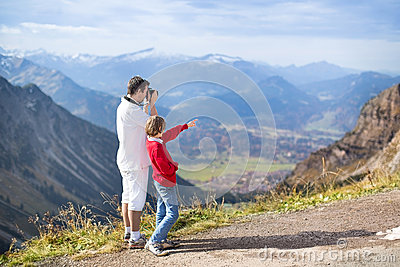 Father and his son taking pictures of mountais