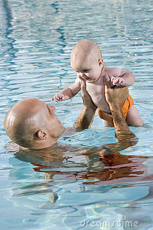 Father holding baby up high in swimming pool