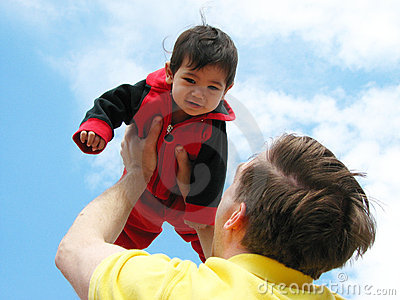 Father holding baby up to sky