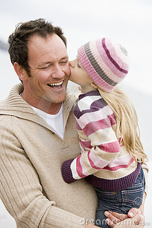 Father holding daughter kissing him at beach