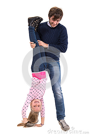 Father holding his smiling daughter upside down