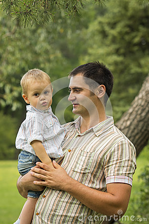 Father holding son in park