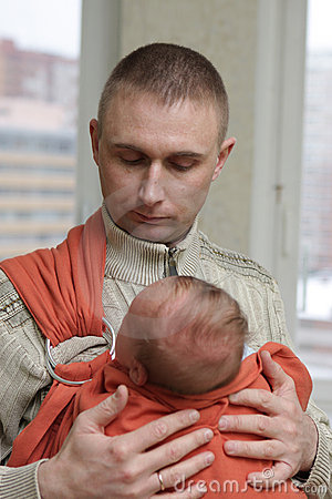 Father holds his baby by sling