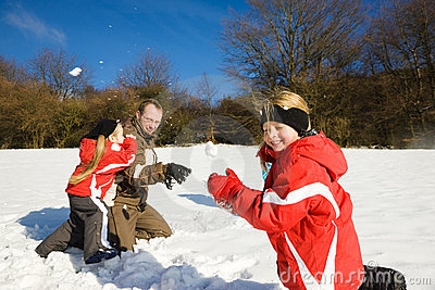 Father with kids having a snowball fight in winter