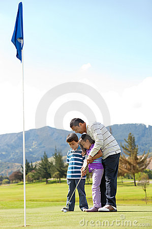 Father and kids playing golf
