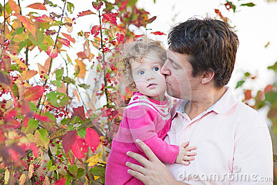 Father kissing his cute daughter in autumn park