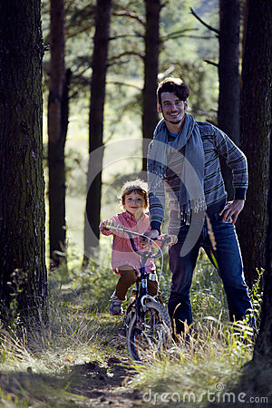 Father learning his son to ride on bicycle outside