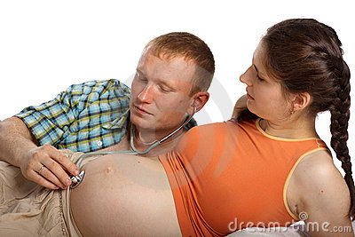 Father listening heartbeat of his future child