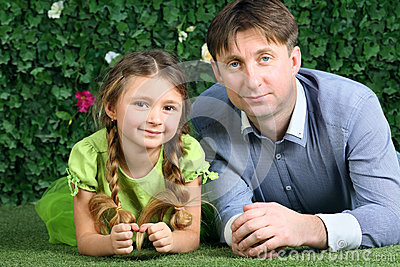 Father and little daughter lie on green grass