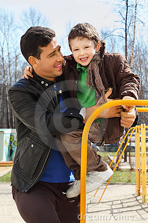 Father and little son play at playground