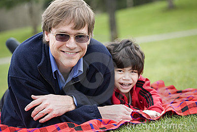 Father lying on blanket with disabled son