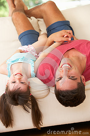 Father Lying Upside Down On Sofa With Daughter