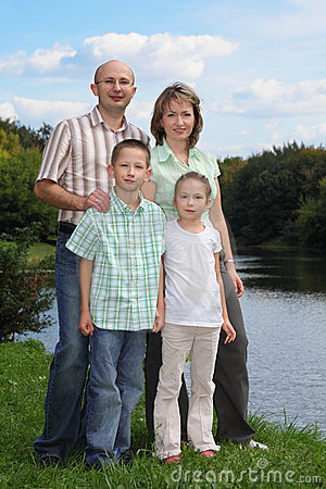 Father, mother, boy and girl is staying near pond