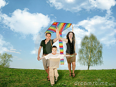 Father, mother and child on grass with kite