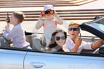 Father, mother and children ride in car