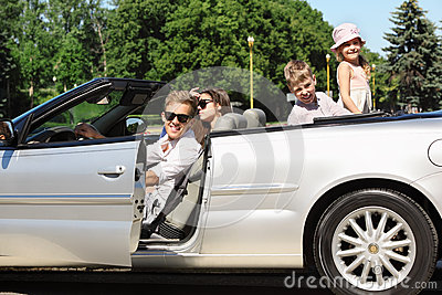 Father, mother and children sit in convertible car