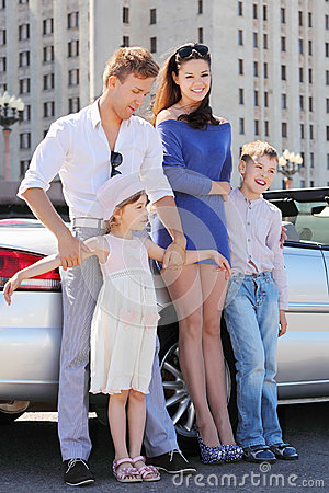 Father, mother and children stand near car