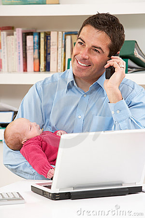 Father With Newborn Baby Working From Home Using L